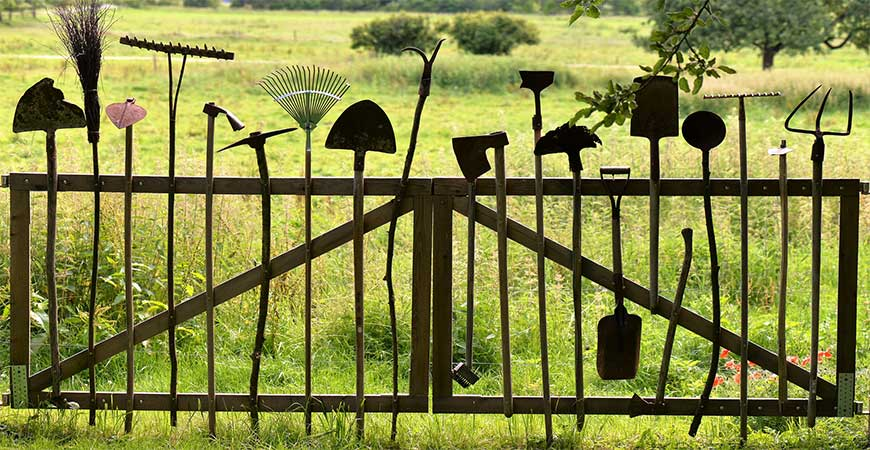 gardening tools on a fence