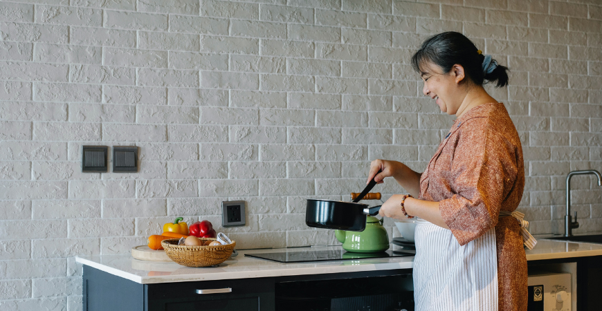 Woman cooking in front of her faux brick backsplash
